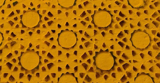 Textura pintada de amarelo com detalhes artesanais. trabalho manual na parede.