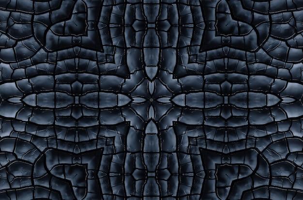 Textura preta de fundo simétrico de madeira queimada. close-up da placa queimada. consequências de um incêndio, o efeito caleidoscópio