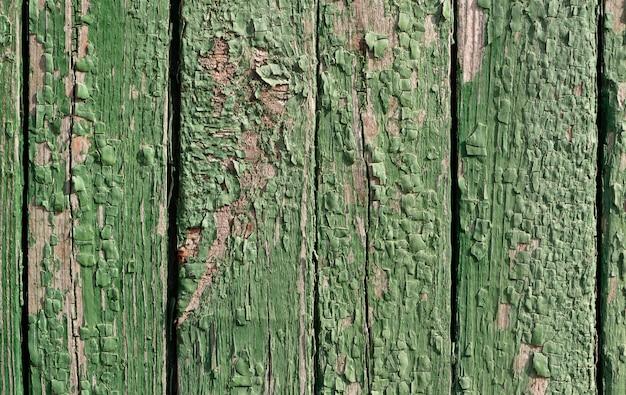 Textura rústica de madeira velha da cerca com pintura verde da casca.