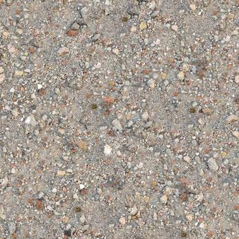 Textura tileable sem costura de fragmento de solo empoeirado com pedaços de detritos - tijolo, coquina, macadame.