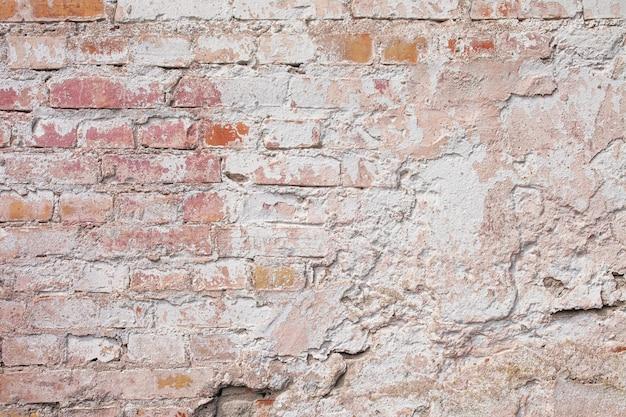 Textura vazia da parede de tijolo velha. superfície de parede suja pintada. fundo de parede de pedra vermelha do grunge. fachada de prédio gasto com gesso danificado.