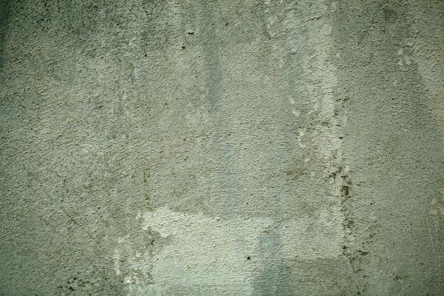 Textura velha da parede exterior pintada de verde com pinceladas e pintura esmaecida em uma exibição de quadro inteiro.