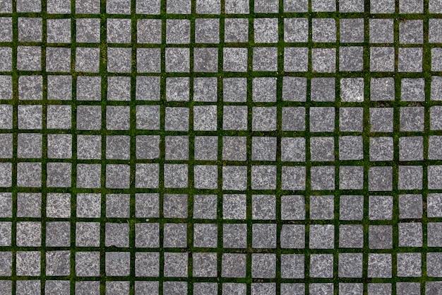 Textura velha de paralelepípedos na cidade velha. fundo do pavimento da cidade. padrão de tijolo de pedra de granito abstrato. textura da calçada da rua