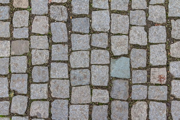 Textura velha de paralelepípedos na cidade velha. padrão de tijolo de pedra de granito abstrato. textura da calçada da rua
