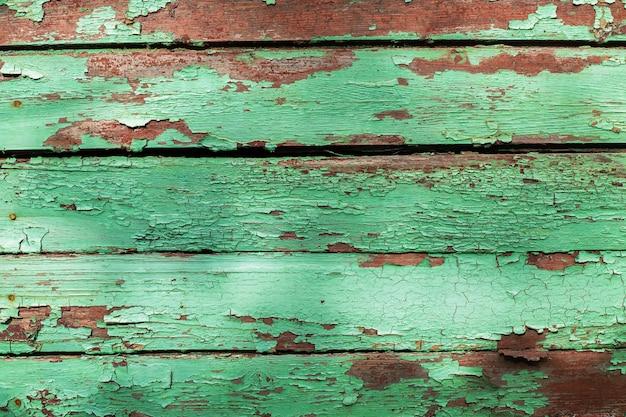 Texture o fundo das pranchas de madeira cobertas com a pintura descascada velha da cor verde