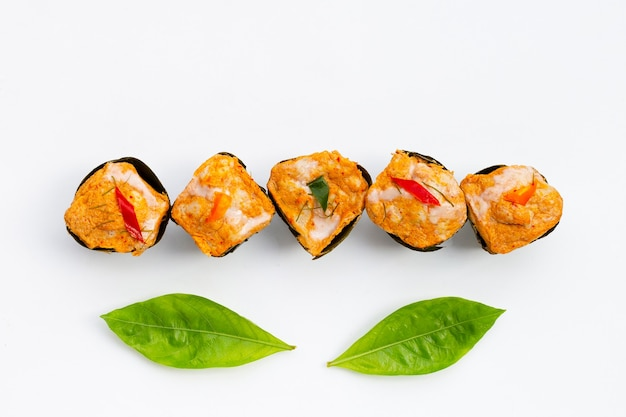 Thai caril de peixe em fluxo contínuo em folhas de bananeira em folhas de noni ou morinda citrifolia em fundo branco.