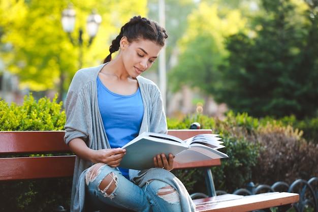 Thouhtful bela garota africana lendo o livro