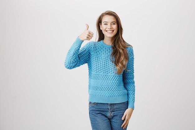 Thumbs up alegre da mulher de apoio na aprovação