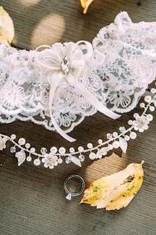 Tiara da liga de noiva na cabeça em penteado anel de casamento contra o fundo de textura de madeira