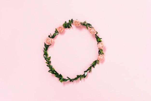 Tiara de rosas artificiais e folhas no fundo rosa