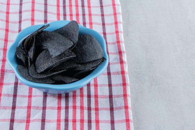 Tigela azul de batatas fritas pretas crocantes e toalha de mesa na pedra.