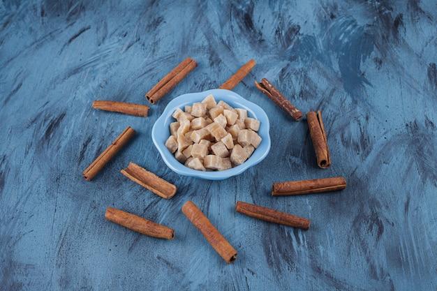 Tigela azul de cubos de açúcar mascavo e paus de canela na superfície azul.