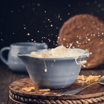 Tigela azul de flocos de milho com respingo de leite