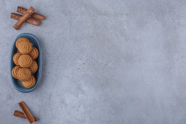 Tigela azul de mini bolos de canela com copo de chá na pedra.