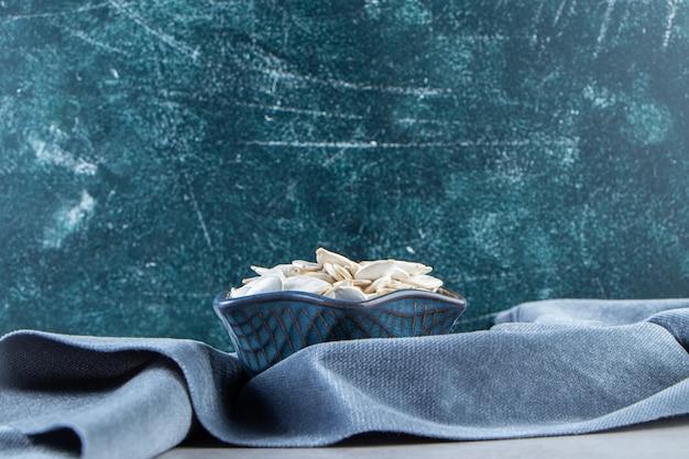 Tigela azul de sementes de abóbora com pano azul sobre fundo de pedra.