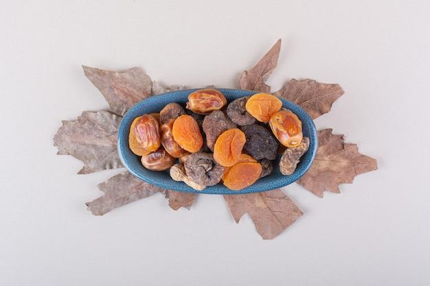 Tigela azul de várias frutas e nozes orgânicas em fundo branco. foto de alta qualidade