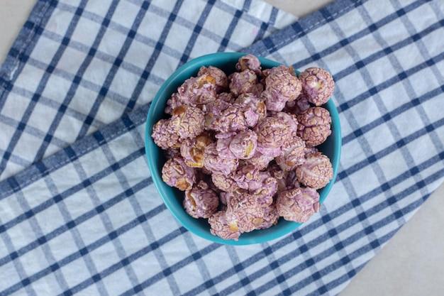 Tigela azul descansando sobre uma toalha dobrada e cheia de pipoca revestida de doces na mesa de mármore.