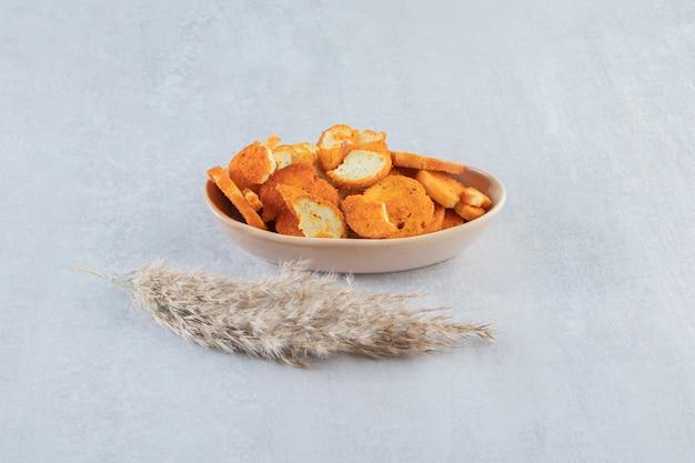 Tigela bege com crostas secas crocantes na pedra.