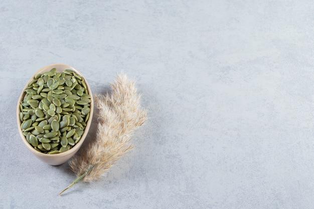 Tigela bege de sementes de abóbora descascadas em fundo de pedra.