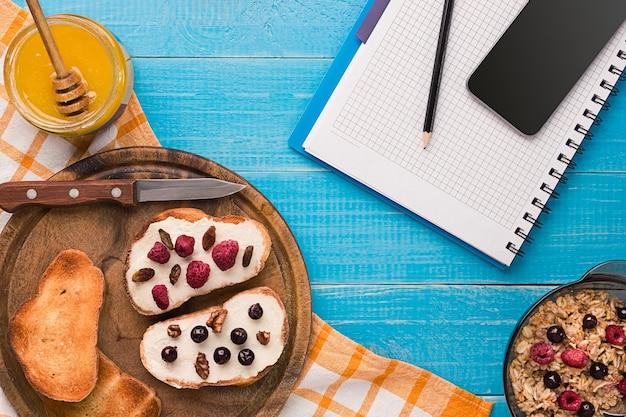 Tigela branca cheia de aveia saudável, com banana, leite e pão seco no café da manhã.
