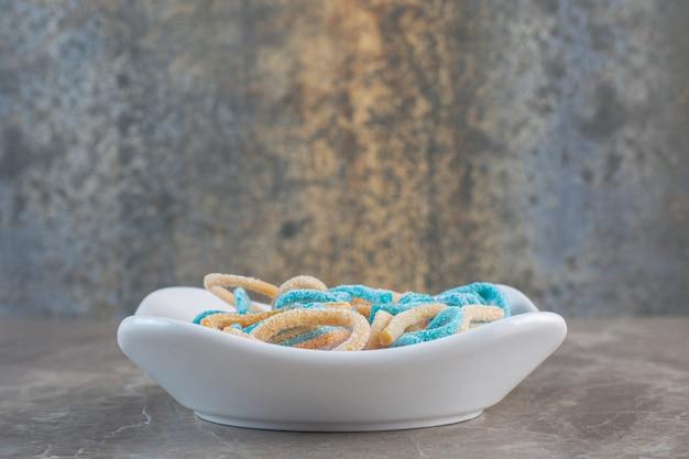 Tigela branca cheia de balas de fita do arco-íris. doces de geleia coloridos fecham-se como um fundo alegre e brilhante.