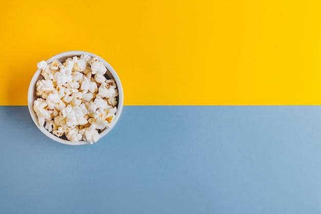 Tigela branca com pipoca em fundo azul e amarelo. plano de diversão do conceito, assistir a um filme ou uma série.