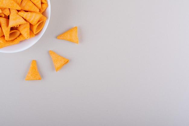 Tigela branca de chips de triângulo em fundo de mármore. foto de alta qualidade