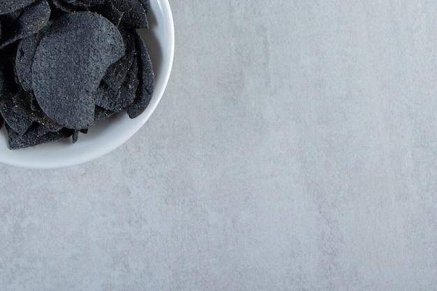 Tigela branca de chips pretos crocantes salgados na pedra.