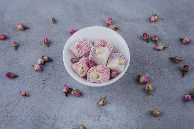Tigela branca de delícias rosa com nozes na pedra.