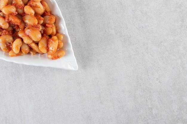 Tigela branca de grãos de soja cozidos colocada em uma superfície de pedra