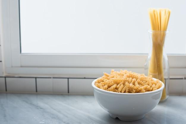 Tigela branca de macarrão espiral e espaguete amarrado erguem-se nas janelas da sala da cozinha