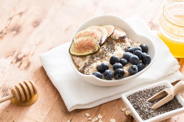 Tigela branca de mingau de aveia com figos, mirtilos e sementes de chia. pequeno-almoço saudável de aveia