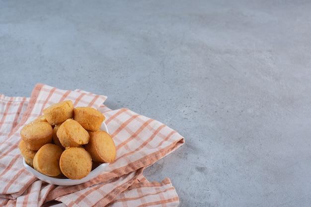 Tigela branca de mini bolos doces na mesa de pedra.