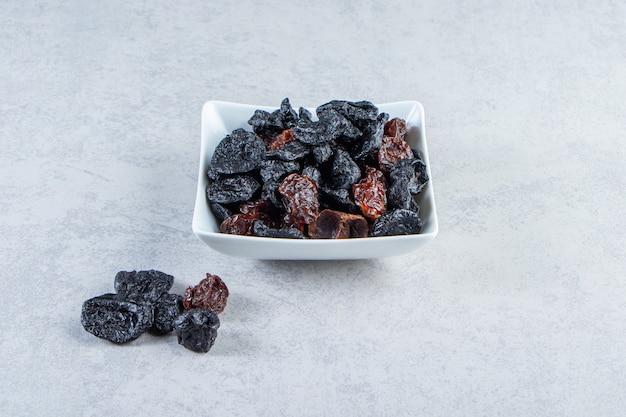 Tigela branca de saborosas tâmaras secas em fundo de pedra.
