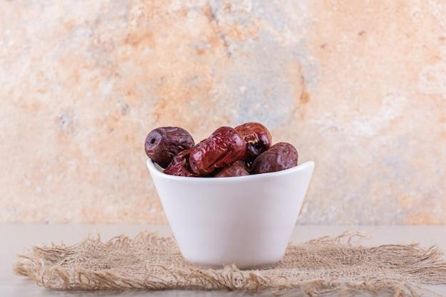 Tigela branca de saborosos frutos secos de amora silvestre em fundo branco. foto de alta qualidade