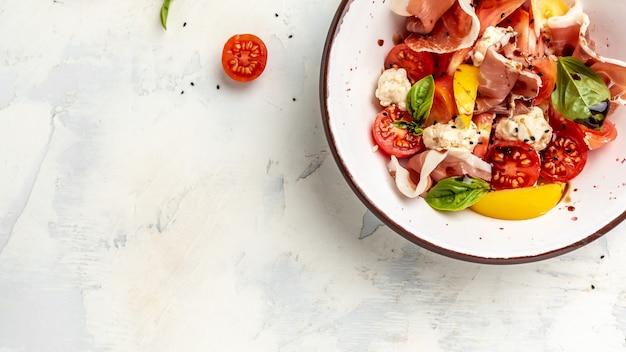 Tigela branca de salada mediterrânea fresca e saudável com tomates, bolinhos de cream cheese, presunto e folhas de manjericão. conceito de deliciosa comida equilibrada. formato de banner longo. vista do topo.