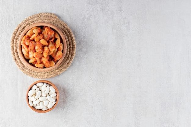 Tigela branca de soja cozida e feijão cru em fundo de pedra.