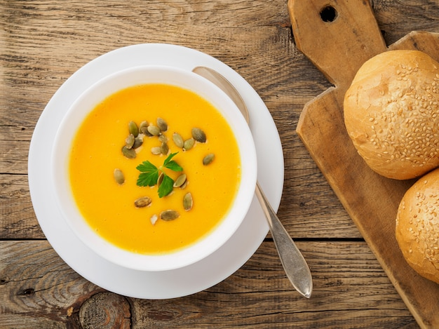 Tigela branca de sopa de abóbora, salsa guarnecida e sementes de girassol no fundo de madeira
