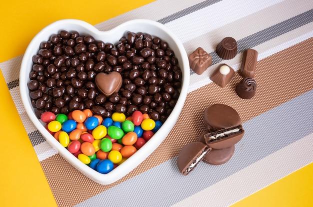 Tigela branca em forma de coração cheia de chocolates marrons e coloridos, avelãs e amêndoas cobertas de chocolate