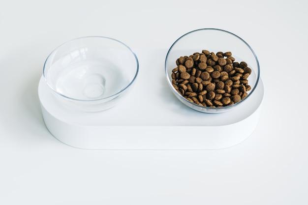 Tigela branca para cão ou gato com ração e água isolada no fundo branco.