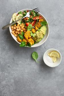 Tigela buddha vista superior equilibrada de comida vegetariana saudável aloo gobi, salada de tabouli, grão de bico, abacate, tomate e espinafre
