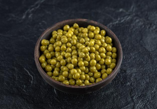Tigela cheia com ervilhas verdes marinadas na mesa preta.