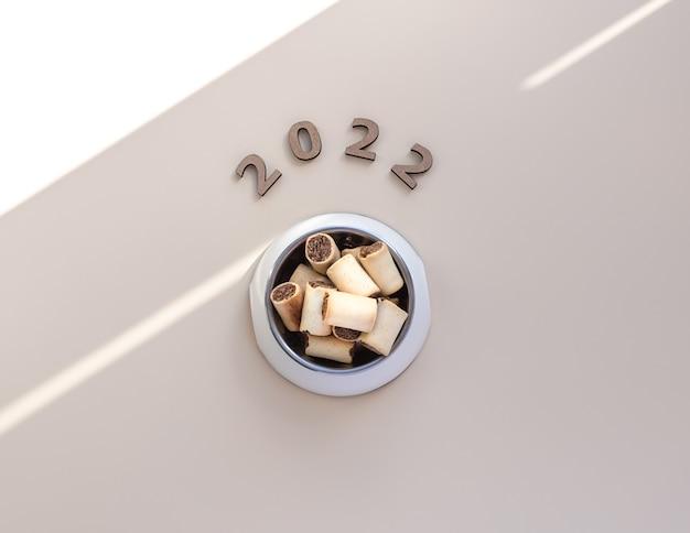 Tigela cheia de comida de cachorro e números 2.022 animais ano novo