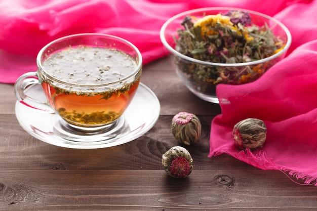 Tigela cheia de ervas aromáticas e chá quente na mesa