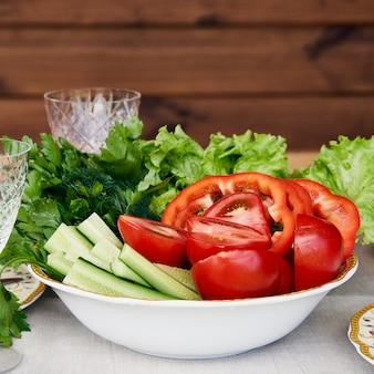 Tigela cheia de legumes frescos na mesa de madeira