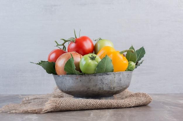 Tigela cheia de pimentão, cebola, tomate vermelho, tomate verde, pepino, cebola roxa e folhas, em mármore.
