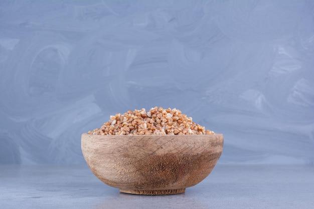 Tigela cheia de trigo sarraceno cozido na superfície de mármore