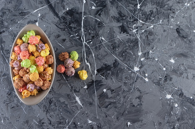 Tigela cinza de deliciosas pipocas coloridas em fundo de mármore.
