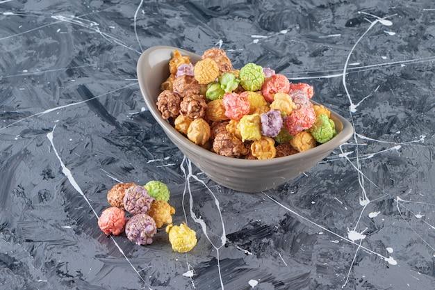 Tigela cinza de deliciosas pipocas coloridas na mesa de mármore.