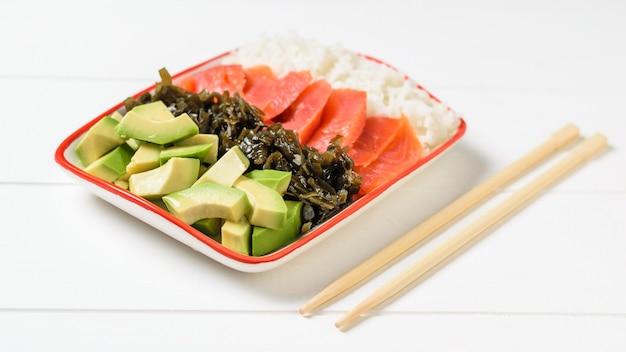 Tigela com arroz, abacate, salmão e alga marinha em uma mesa branca.